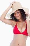 Attractive brunette woman holding her hat