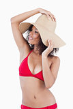 Attractive young woman looking away while holding her hat