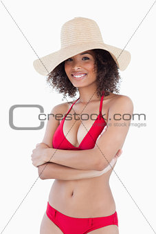 Smiling woman standing in swimsuit with arms crossed