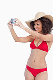 Young woman in beachwear photographing herself