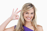 Smiling young blonde woman making the ok sign