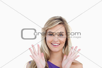 Smiling woman showing her surprise with hands raised