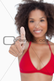 Thumbs up being shown by a young brunette woman