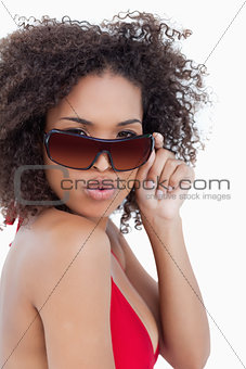 Young woman puckering her lips while holding her sunglasses