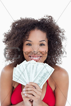 Smiling brunette holding a fan of bank notes