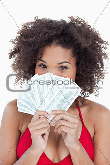 Brunette woman hiding her face behind a fan of notes