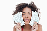 Young attractive woman puckering her lips while holding bank not
