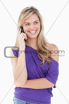 Smiling blonde woman using her mobile phone