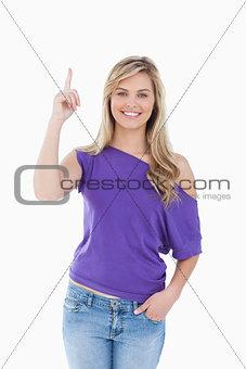 Smiling blonde woman raising her finger