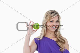 Smiling blonde woman holding a green apple