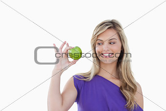 Happy young blonde woman looking at a green apple