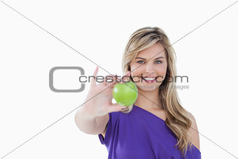 Smiling blonde woman holding a delicious green apple