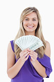 Happy blonde woman holding a fan of notes