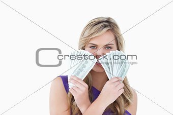 Young blonde woman holding two fans of notes