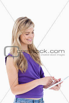 Smiling blonde woman using a tablet computer