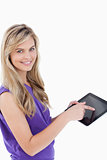 Happy blonde woman looking at the camera while using her tablet 