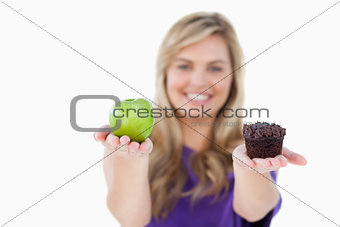 A fruit and a muffin being held by a blonde woman