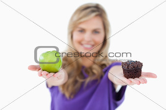 A green apple and a muffin being held by a young woman