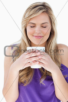 Young woman smelling her cup of coffee