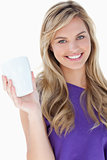 Smiling blonde woman holding a cup of coffee