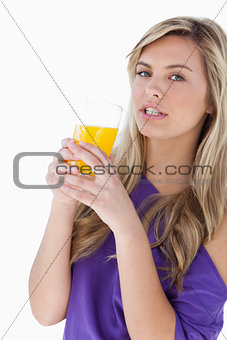 Attractive blonde woman holding an orange juice