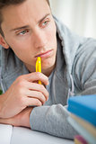 Close-up of a depressed student chewing his pencil 