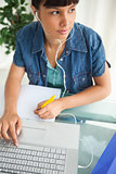 Female student looking away while doing her homework