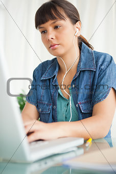 Female student doing her homework with music