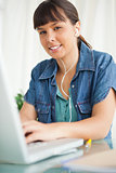 Portrait of a female student doing her homework with music