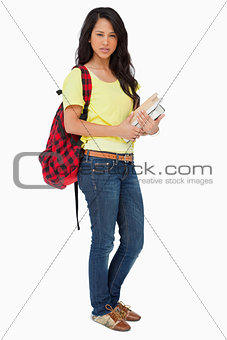 Beautiful Latin student with backpack holding textbooks