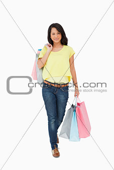 Beautiful Latin student walking with shopping bags