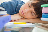 Female student sleeping among her books