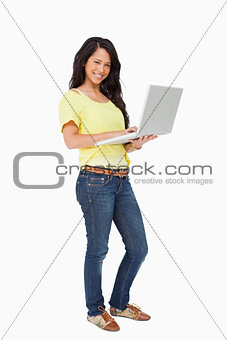 Portrait of a smiling Latin student standing with a laptop