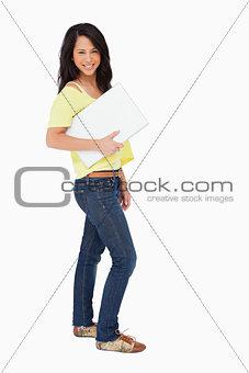 Beautiful Latin student holding a laptop