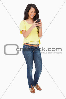 Beautiful Latin laughing while using a smartphone
