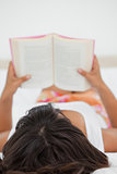 Rear view of a young woman reading a book
