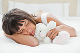 Young woman sleeping with a teddy bear