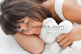 Beautiful young woman sleeping with a teddy bear