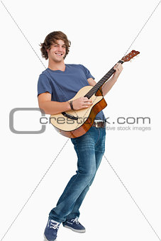 Male student posing while playing guitar