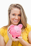 Close-up of a piggy-bank holding by a blond woman