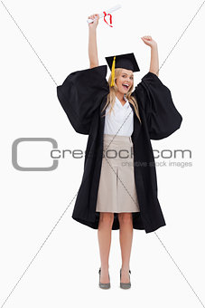 Blonde student in graduate robe holding up her diploma