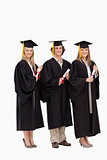 Three smiling students in graduate robe holding a diploma