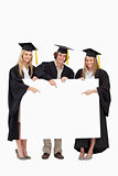 Three students in graduate robe holding and pointing a blank sig