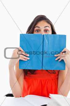 Portrait of a student hiding behind a blue book