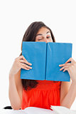 Portrait of a student winking behind a blue book