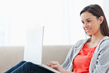 A woman lying on the couch smiling with her laptop