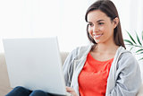 A woman with a lovely smilw using her laptop