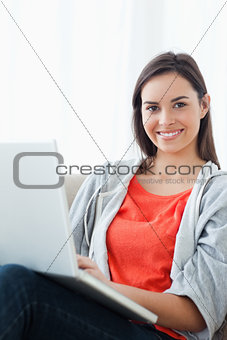 A brightly smiling woman using her laptop