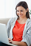 Close up of a woman looking at her laptop while lying on the cou