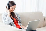 A woman on the couch with her laptop and listening to headphones